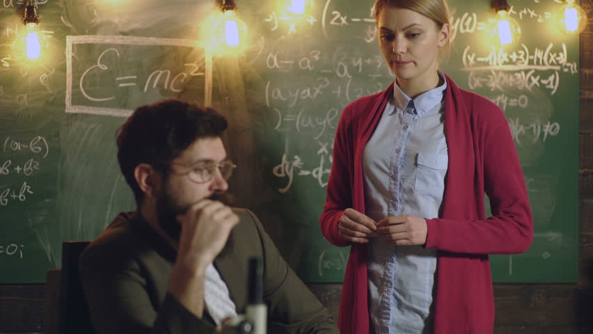 Teachers work on chalkboard background. Teacher and student. Learning concept. Teacher is sitting at the table in classroom. Student communicates with bearded professor on background of chalkboard