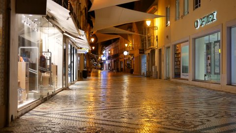 Faro, Portugal - September 4 2017: Retail area street at night with shops and cobblestone street in Faro, Algarve, Portugal