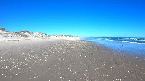 Sand and seashells Texas ocean beach driving POV. Beautiful southern Texas, Gulf of Mexico Ocean beach. Padre Island, Mustang Island, Corpus Christi.  Waves and surf on sand.