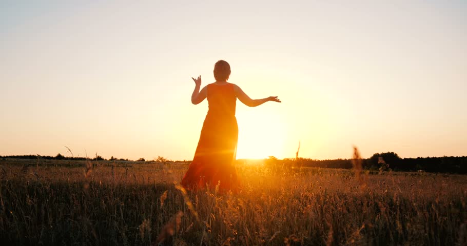 Beautiful middle-aged woman dancing in a field at sunset in slow motion | Shutterstock HD Video #1025708930