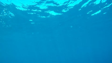 A view from a scuba diver of surfacing from under the water.