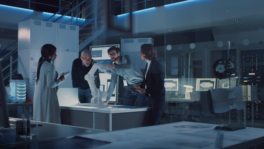 Engineers Meeting in Robotic Research Laboratory: Engineers, Scientists and Developers Gathered Around Illuminated Conference Table, Talking, Using Tablet and Analysing Design of Industrial Robot Arm | Shutterstock HD Video #1025767460