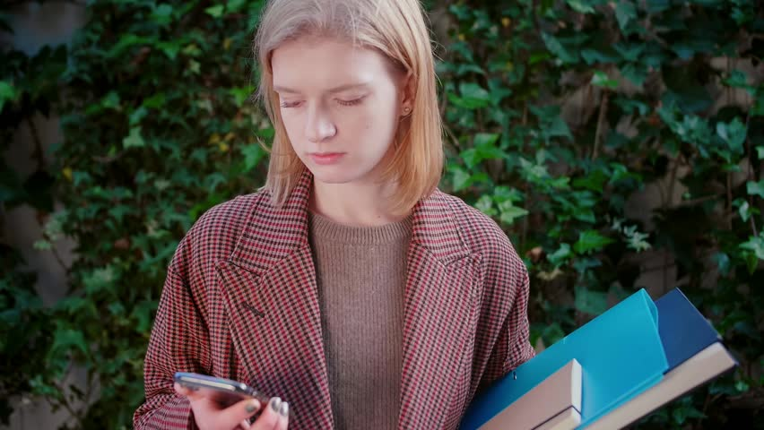 Nerd student blond cute girl using mobile phone or smartphone checking mail publishing post on social network website or app feel distracted disappointed and bored background leaves on concrete wall | Shutterstock HD Video #1025794100