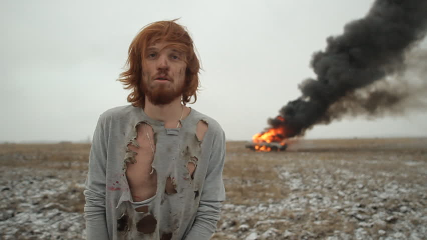 Surviving man on the background of a burning car in the field. Car crash