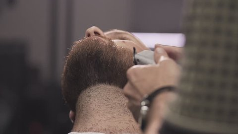 Barber shaving beard with electric razor and comb in male salon. Close up of male barber trimming beard with shaver. Professional shaving bearded man in slow motion