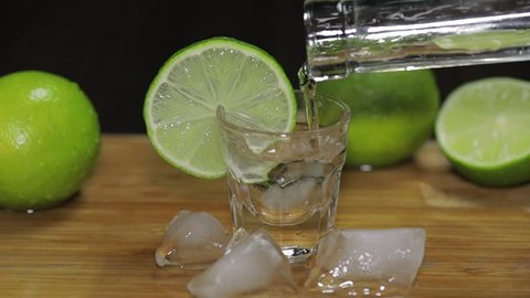 Pouring vodka or tequila from a bottle into shot glasses with ice cubes. Slow motion