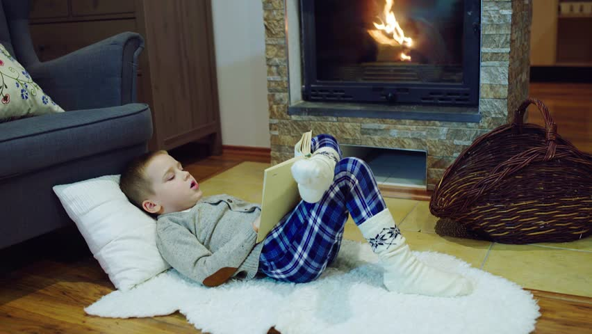 Happy child reading a book at home, near the fireplace, Christmas time | Shutterstock HD Video #1025842400