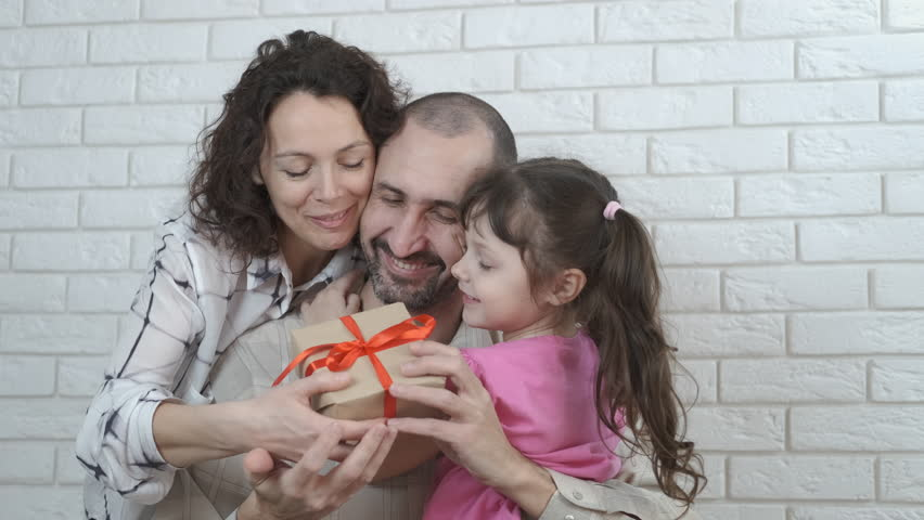 Dad's birthday. The family gives a gift to the father. | Shutterstock HD Video #1025865920
