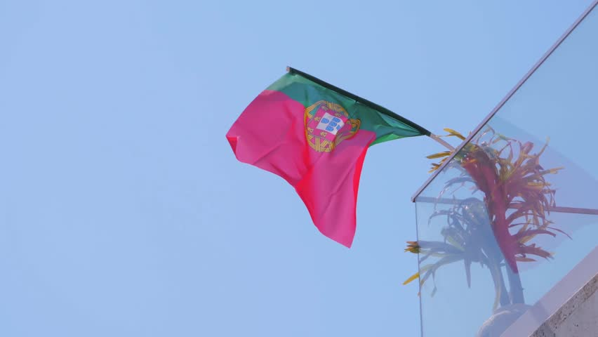 Portugal flag fixed on glass house balcony and fluttering on wind against blue sky   Shutterstock HD Video #1025866700