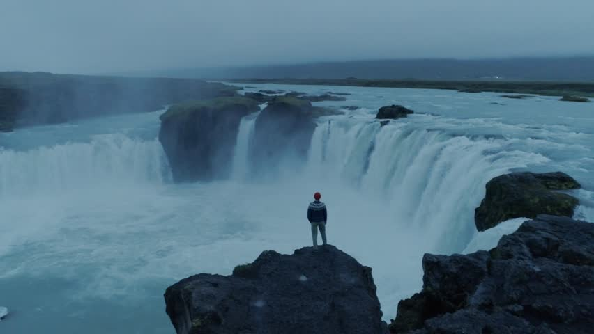 Aertial footage of drone fly around confident, brave and independent contemporary man, hipster intellectual nomad traveller stand on cliff or edge of waterfall in dusk, look ahead for new adventures | Shutterstock HD Video #1025887850