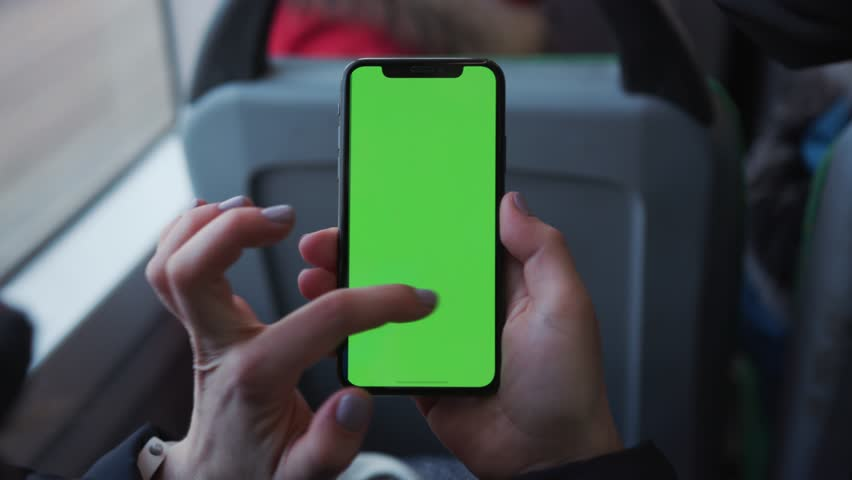 Lviv, Ukraine - May 19, 2018: Woman's hand holding use touch a mobile telephone with a vertical green screen in tram chroma key smartphone technology cell phone street touch message display hand | Shutterstock HD Video #1025899460
