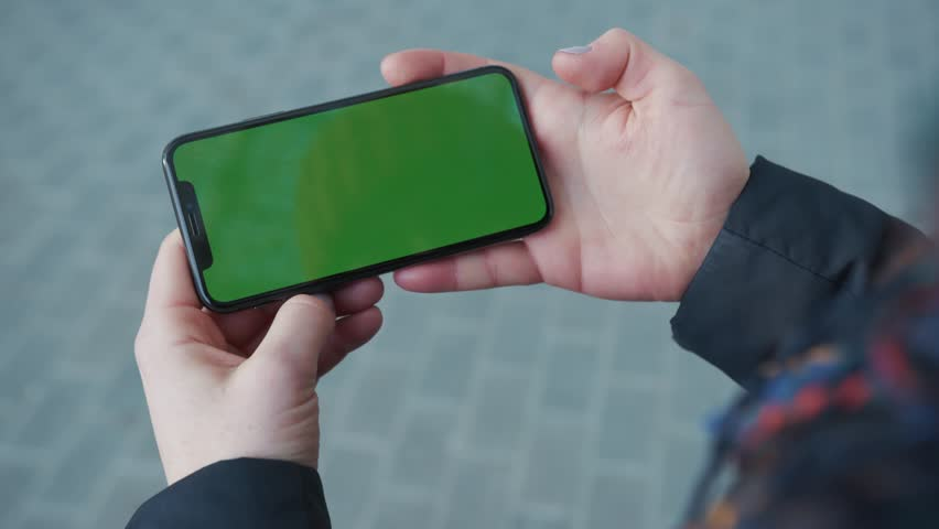 NEW YORK - April 5, 2018: Slow motion hands woman holding phone with horizontal green sceen on busy street background pavement scrolling pages swiping surfing internet technology chroma key message | Shutterstock HD Video #1025899490