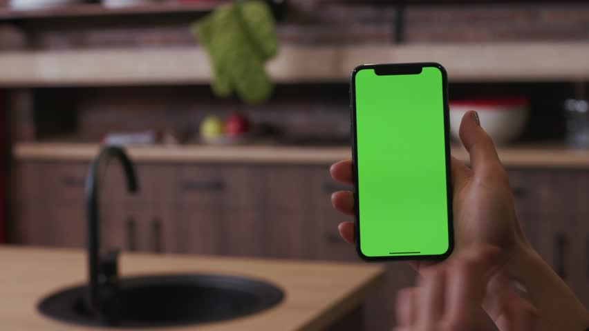 Tokio, Japan - April 7, 2018: Close up woman hand hold use touch phone with vertical green screen kitchen at home breakfast browse business food girl house shop healthy internet abstract slow motion | Shutterstock HD Video #1025899520