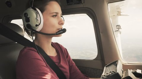 Young girl piloting a small plane through turbulence talking on intercom