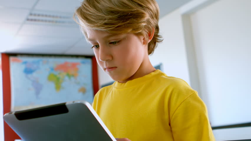 Front view of cute Caucasian schoolboy using digital tablet in a classroom at school. He is studying and learning 4k | Shutterstock HD Video #1025908340