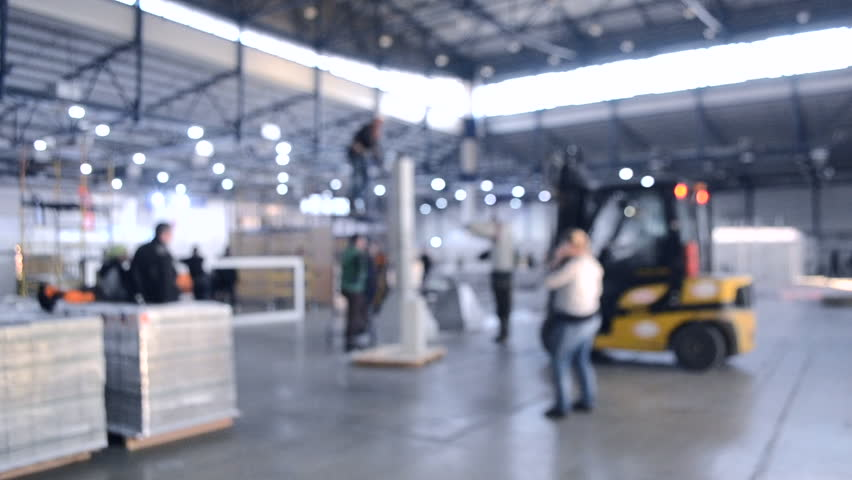 Construction works inside large building. Building installation exhibition center. Loader machine on the construction site. Many people in installation work. Blurred Background | Shutterstock HD Video #1025911400