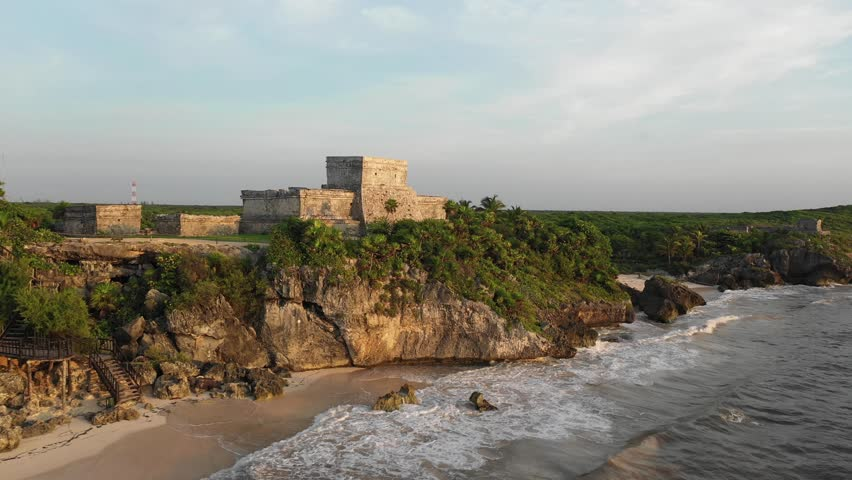 Aerial view of Mayan temple shot over sea in Tulum Mexico at golden hour