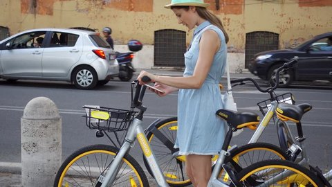 ROME, ITALY - CIRCA May 2018: Woman in blue dress and hat hiring city bike on bicycle parking. Female traveler renting stationless oBike bicycles in Rome, Italy via mobile gps location app