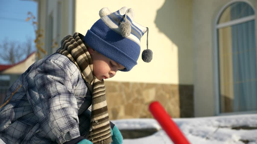 Little Boy Plays With Toy Trucks on Snow in Backyard Garden. Cold Weather on Winter Holidays. Bright Sunny Day. Slow motion 0.5 speed 60 fps | Shutterstock HD Video #1025946980