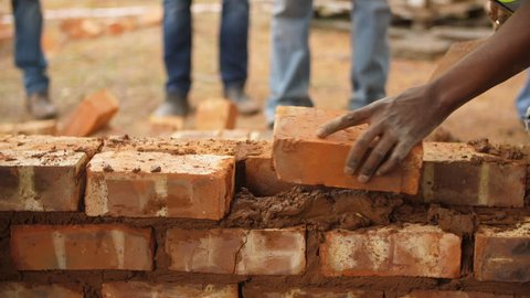 Black male volunteer worker lays brick into wall with cement using trowel