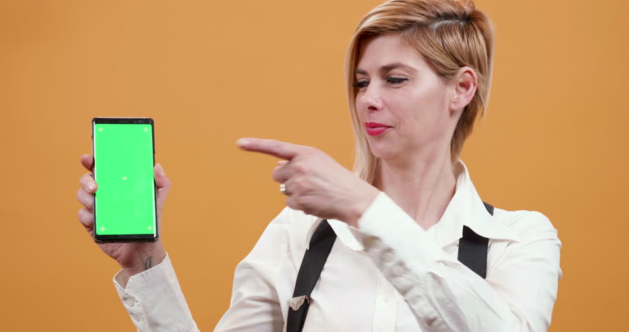 Woman pointing her finger to a smartphone with green screen on. Portrait of a smiling showing at green screen over yellow background. | Shutterstock HD Video #1025975360