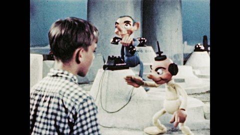 1940s: Puppet hangs up phone and marionette speaks to boy. Boy speaks. Puppet with mustache speaks. Boy speaks. Marionettes run from phone to phone book.