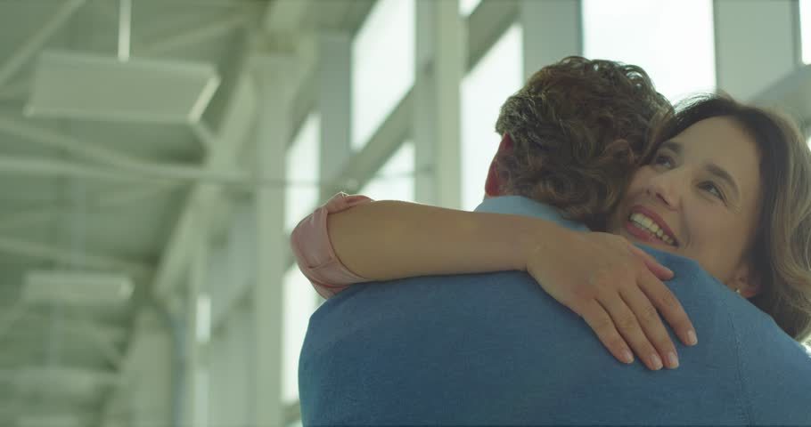 Back view of the Caucasian man hugging his pretty happy wife or girlfriend when they meeting in the airport. Rear. | Shutterstock HD Video #1026000440