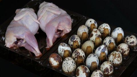 Fresh meat of quail in a plastic brown tray next to the quail eggs on a black background. Female hands take eggs from the tray