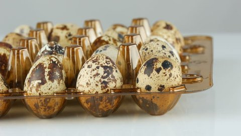 Fresh meat of quail in a plastic brown tray next to the quail eggs on a white background