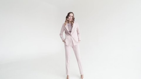 Business lady posing in a white jacket and trousers on a white background. Sexy woman in white suit goes ahead, 50 frames per second
