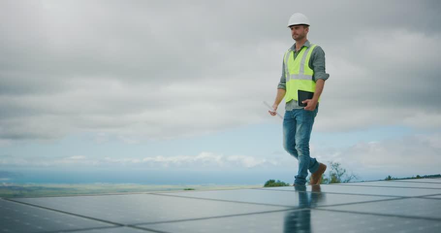 Sustainable green energy jobs, solar panel technician surveying solar panels #1026077900