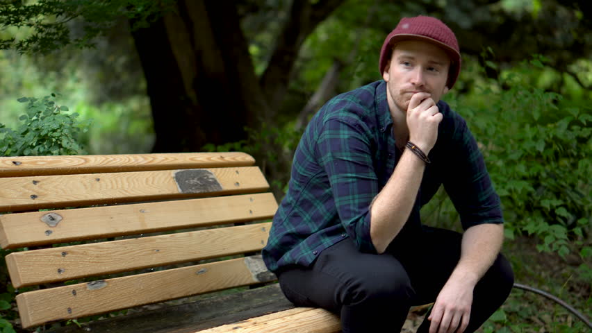 Young Man Sitting Down on Park Bench to Think About Things | Shutterstock HD Video #1026086360