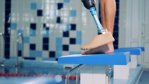 Man with prosthetic leg stands near a pool while training.
