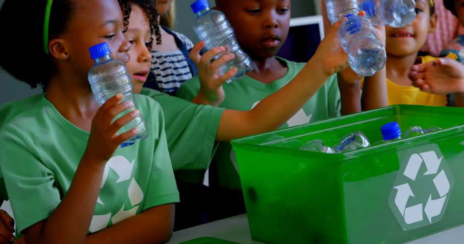 Front view of group of diverse schoolkids putting bottles in recycle container at desk in classroom. They are studying about green energy and recycle. | Shutterstock HD Video #1026122180