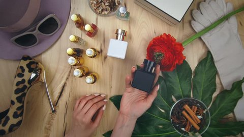 Top view of young woman choosing perfume. Different bottles of perfume on table