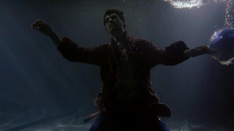 body of sunken man is falling on bottom of river in darkness, mermaid is swimming to him, underwater
