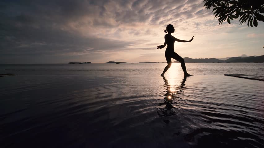 Silhouette of young woman exercising on sunrise time by practicing chinese Tai Chi at beach. Shot in 4k resolution #1026167480