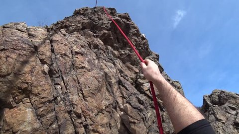 Climber climbs the rock. First person view. The camera on the helmet. Extreme climbing. Visible rope, hands and bare stones. Gray rock. Danger of falling. Steep cliffs and heights. Achieving goal.