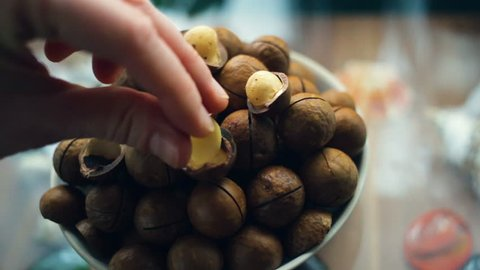 hand puts the kernel of the macadamia nut. A handful of macadamia in a plate close-up. The hand rotates the plate around its axis. Natural light, indoors, real time.