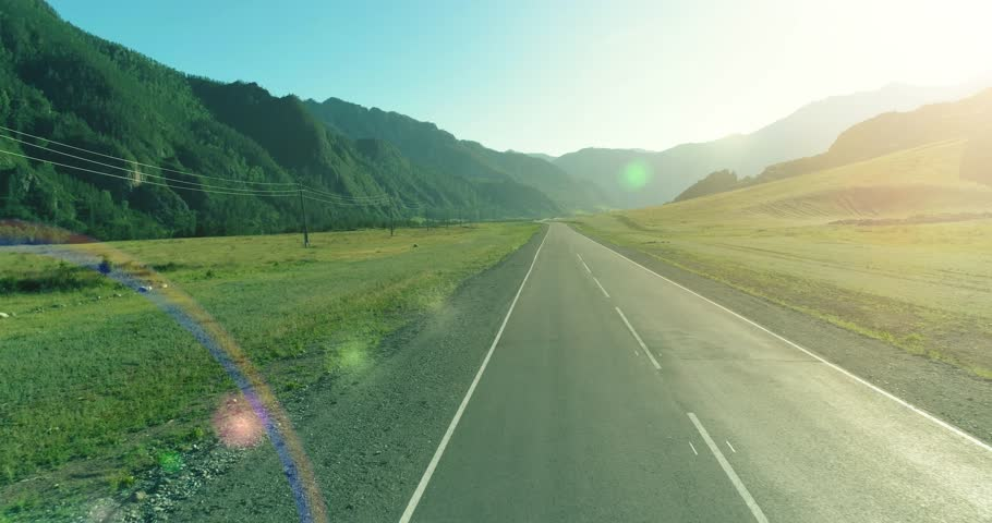 Aerial low air flight over mountain perfect asphalt highway road and meadow at sunny summer morning. Near green trees. Fast horizontal movement with sun rays. #1026235670