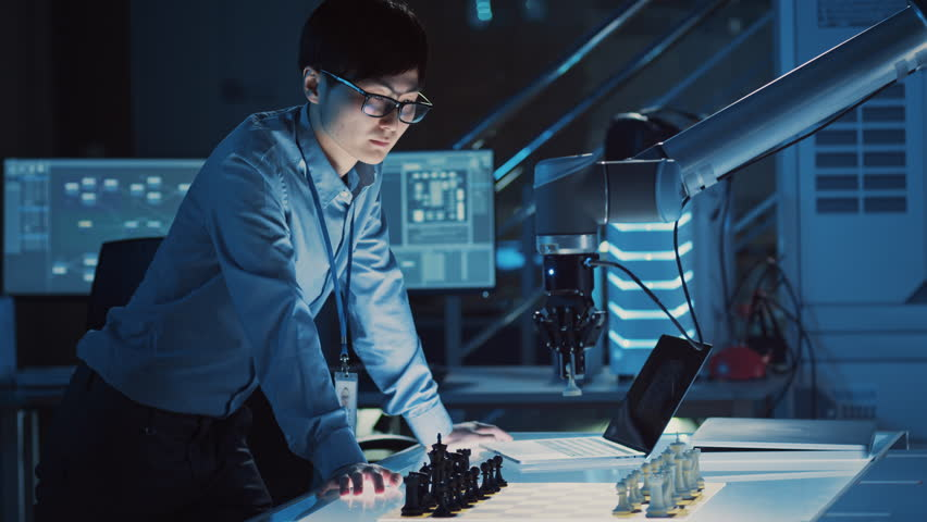 Professional Japanese Development Engineer is Testing an Artificial Intelligence Interface by Playing Chess with a Futuristic Robotic Arm. They are in a High Tech Modern Research Laboratory. | Shutterstock HD Video #1026241850