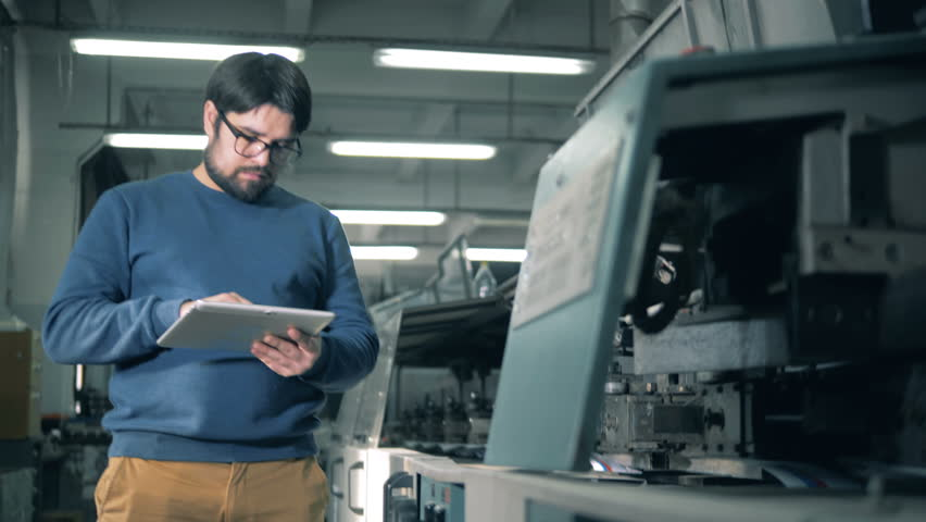 Man with a tablet computer is inspecting a functioning printing equipment | Shutterstock HD Video #1026251090