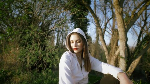 A beautiful young brunette girl with a white hooded sweatshirt looks at you serious and provocative and with beautiful red lips surrounded by nature