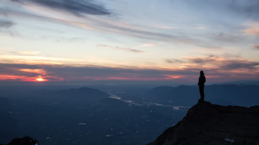 Cinemagrap of Adventurous man standing on top of mountain and enjoying the beautiful view during a vibrant sunset. Taken on top of Cheam Peak in Chilliwack, East of Vancouver, BC, Canada. Animation | Shutterstock HD Video #1026297470