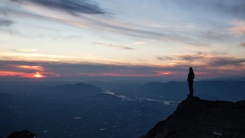 Adventurous man is standing on top of the mountain and enjoying the beautiful view during a vibrant sunset. Taken on top of Cheam Peak in Chilliwack, East of Vancouver, BC, Canada. Animation