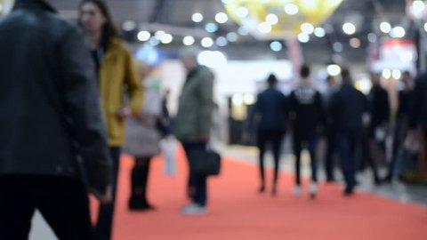 Crowd of people inside building with illumination. Blurred Background. Crowd of people indoors. Blurred Abstract Background. City center. Blurred View of People.