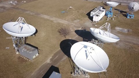 Aerial drone footage of an array of large satellite dishes or radio telescopes pointed skyward.