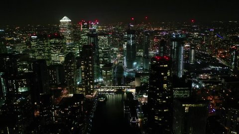 Docklands, London / United Kingdom - March 18 2019: Aerial bird's eye panoramic night video taken by drone of iconic Canary Wharf skyscraper complex and business district, Isle of dogs