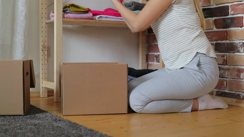 Woman is putting clothes in donation cardboard box at home