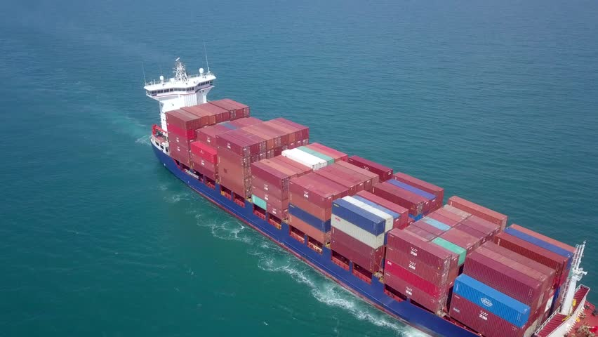 Mediterranean Sea - March 20, 2019: Large container ship cruising slowly at sea, loaded with various container brands, Aerial footage. #1026411470